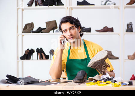 Young man repairing shoes in workshop - Stock Photo