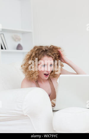 Good looking enthusiastic blonde female relaxing with her laptop while sitting on a sofa in her appartment - Stock Photo