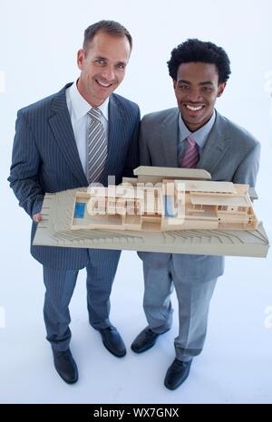 Happy architects holding a model house - Stock Photo