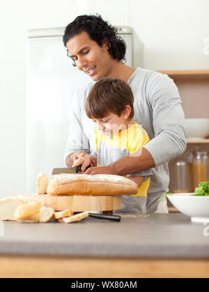 Attentive father helping his son cut some bread in the kitchen - Stock Photo