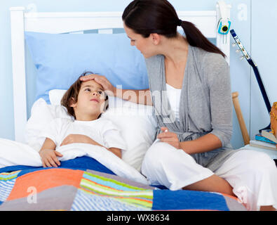 Mother taking her son's temperature lying in bed - Stock Photo