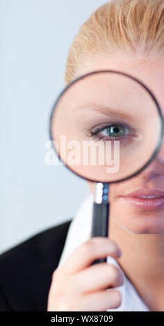 Young Serious Business woman looking through a magnifying Glass - Stock Photo