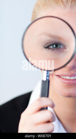 young attractive Smiling woman looking into a magniying glass - Stock Photo