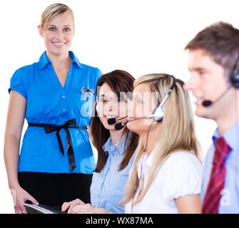 Brunette woman with her colleagues in a call center looking at the camera - Stock Photo