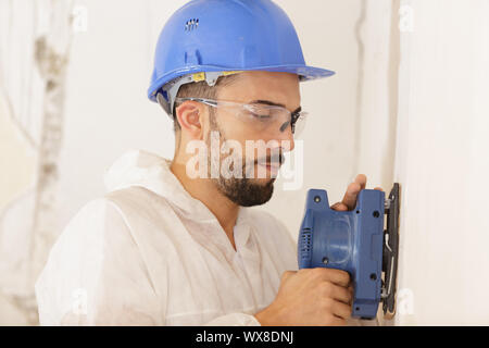 close up of builder working with grinding tool - Stock Photo