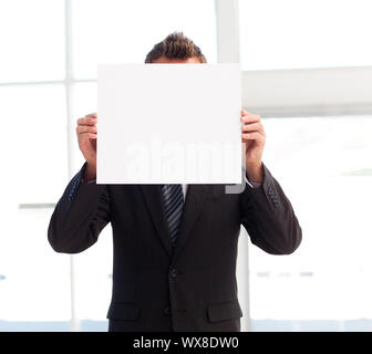 Businessman holding a big white card in front of his face - Stock Photo