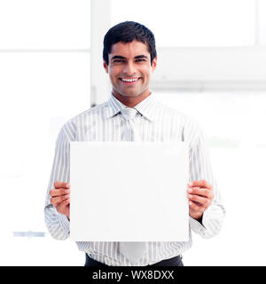 Portrait of a smiling businessman holding a big white card - Stock Photo