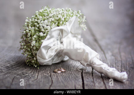 Wedding  bouquet and rings on a dark wooden background. - Stock Photo
