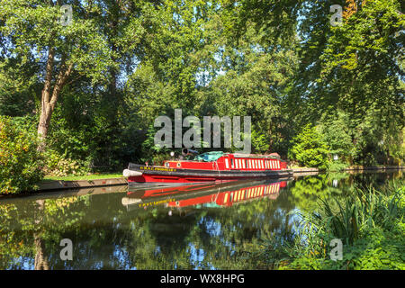 Traditional red narrowboat moored on the banks of the Basingstoke Canal in the Woodham area of Woking, Surrey, southeast England, UK - Stock Photo