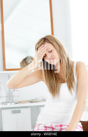 Dejected woman having a headache sitting in the bathroom at home - Stock Photo