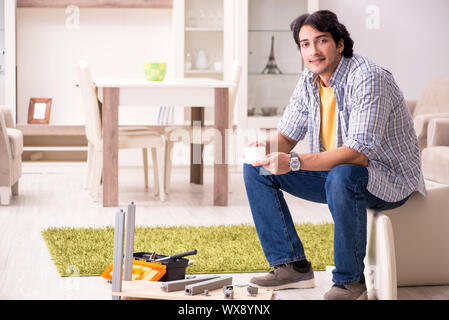 Young handsome man repairing chair at home - Stock Photo