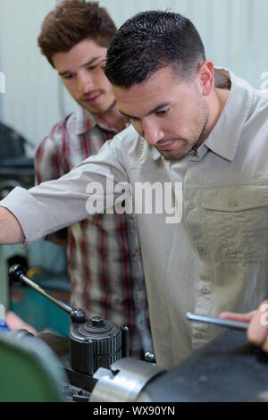 man with apprentice looking at engine - Stock Photo