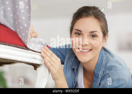 happy woman fixing a chair - Stock Photo