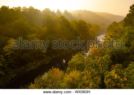 Magical sunrise over deep foggy autumn forest along a river. First rays of sun through fog and trees on slopes. Scenic park fall - Stock Photo