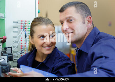 engineer showing female apprentice how to operate machinery - Stock Photo