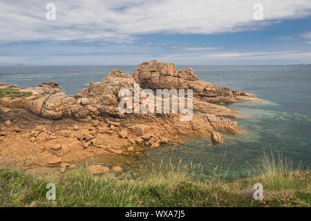 A peninsula of craggy rock rises from the sea along Brittany's Pink Granit Coast, the Côte de granit rose,  near Ploumanach, France. - Stock Photo