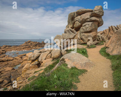 Path between giant boulders above the craggy rocks above the sea along Brittany's Pink Granit Coast, the Côte de granit rose, near Ploumanach, France. - Stock Photo