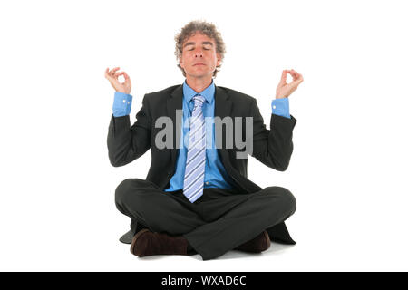 business man sitting on floor in meditation - Stock Photo