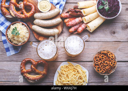 Octoberfest party dinner, Bavarian sausages, pretzels, beer, chilly cheese, cabbage salad, mustard sauce, bacon and traditional spaetzle, flat lay top - Stock Photo