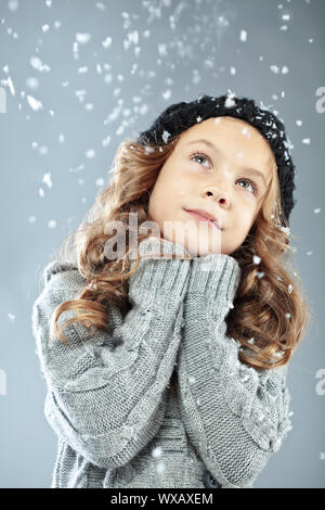 Winter portrait of cute little girl wearing warm cosy clothes studio shot with snow - Stock Photo