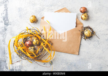 Easter Eggs in bird Nest. Quail easter eggs with feathers in nest on white table with copy space. - Stock Photo