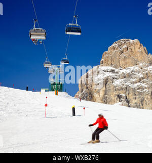 Skier going down the slope under ski lift at Sella Ronda ski route in Italy - Stock Photo