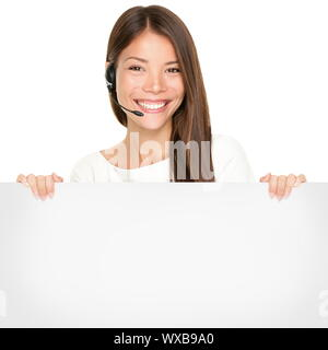 Beautiful Asian woman with a lovely smile wearing a headset and microphone holding a blank white sign in her hands for your advertising or text isolat - Stock Photo