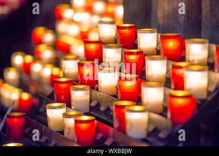Burning candles in catholic church - Stock Photo