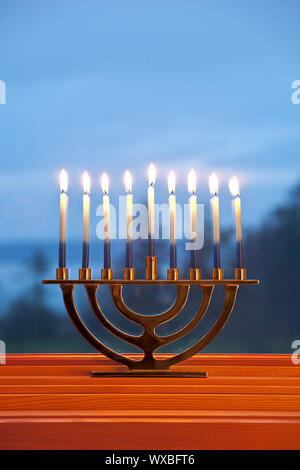 Lighted candles burning in traditional Jewish menorah for Jewish Hanukkah chanukkiah holiday with blue background - Stock Photo