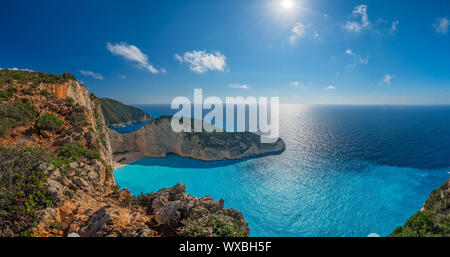 Panoramic view of the sun shining over cliffs in Shipwreck Cove - Stock Photo