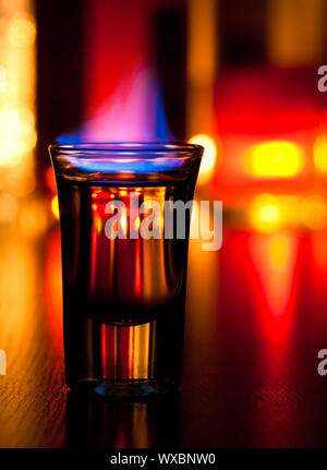 Burning cocktail in shot glass on a table, shallow focus - Stock Photo