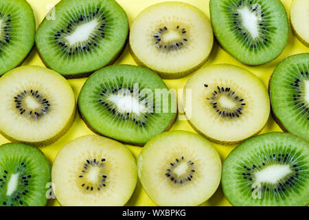 selection of slices of yellow and green kiwi fruit on a bright high contrast yellow background