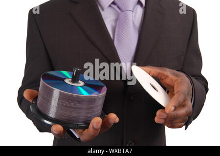 This is an image of a business man holding a stack of DVDs/CDs. This can be used to represent 'Data Service' , 'Software Backup', 'Information Technol - Stock Photo