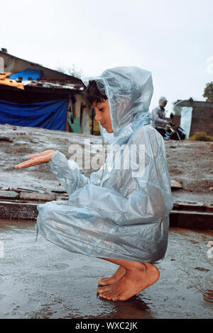 An indian boy wearing rainbows in wet water, village view - Stock Photo