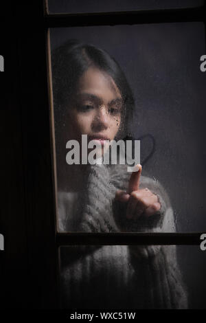 Portrait of woman drawing heart on wet window, focus on rain drop - Stock Photo