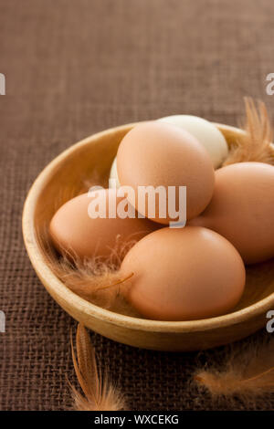 Fresh chicken eggs in wooden bowl - Stock Photo