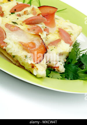 Omelet with Bacon and Sausage, Spring Onion, Leek, Greens closeup on Green Plate - Stock Photo