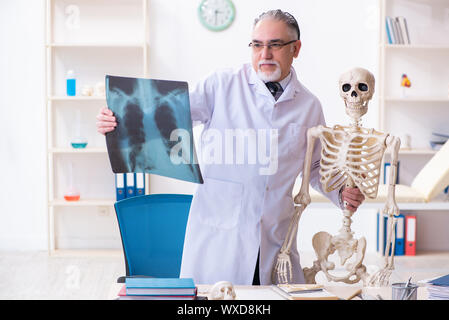 Aged male doctor with skeleton - Stock Photo