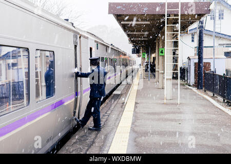 DEC 1, 2018 Hakodate, JAPAN - JR Suoer Hokuto train stop at Onuma Koen station  platform during snow fall in winter with train conductor staff stand a - Stock Photo