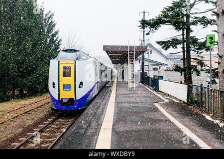 DEC 1, 2018 Hakodate, JAPAN - JR Suoer Hokuto train stop at Onuma Koen station  platform during snow fall in winter foggy atmosphere - Stock Photo