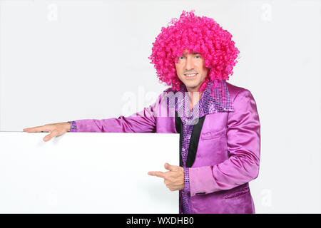 Man in bright suite wearing wig holding message, board - Stock Photo