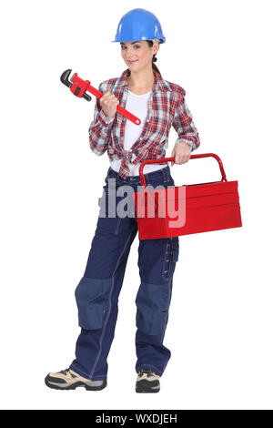 A tradeswoman holding a pipe wrench and toolbox - Stock Photo