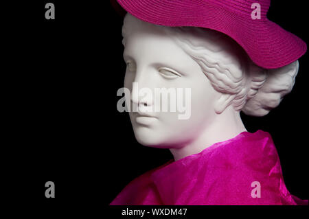 Plaster copy of ancient statue head in pink hat and scarf on a black background. Gypsum sculpture female face. - Stock Photo