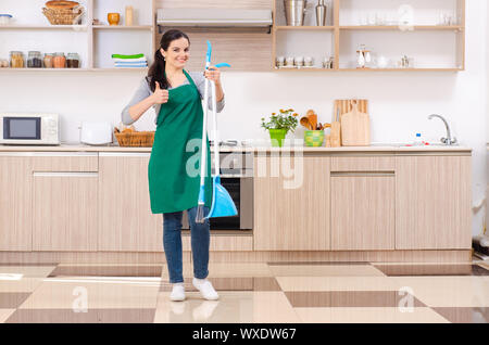 Young female contractor doing housework - Stock Photo