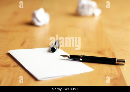 pen and paper in a wooden desktop showing creativity concept - Stock Photo