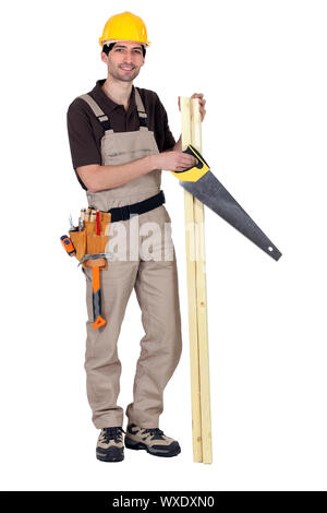 Worker holding plank of wood and hand-saw - Stock Photo