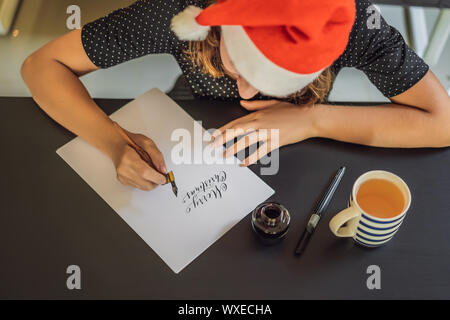 Merry christmas and a happy new year. Calligrapher Young Woman writes phrase on white paper. Inscribing ornamental decorated letters. Calligraphy - Stock Photo