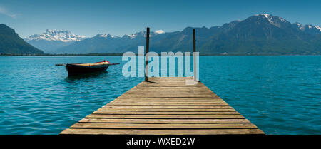 Montreux, VD / Switzerland - 31 May 2019: mountain and lake landscape with a vintage rescue rowboat - Stock Photo