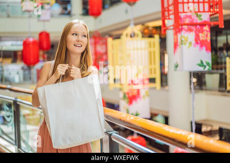 Woman hold shopping bag against the background of Chinese red lanterns for the Chinese New Year. Big sale in honor of the New Year's Eve. Black - Stock Photo