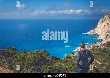 Tourist admiring view on the viewpoint above Navagio Beach - Stock Photo